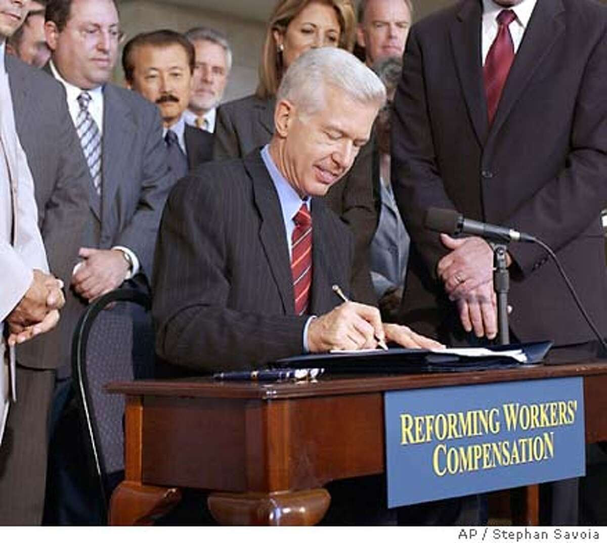 Gov. Gray Davis signs a Workmens Compensation Bill into law during a ceremony at the Los Angeles Chamber of Commerce Tuesday, Sept. 30, 2003, in Los Angeles. Davis pledged the package will reduce high premiums for businesses -a key issue in the recall campaign. (AP Photo/Stephan Savoia)