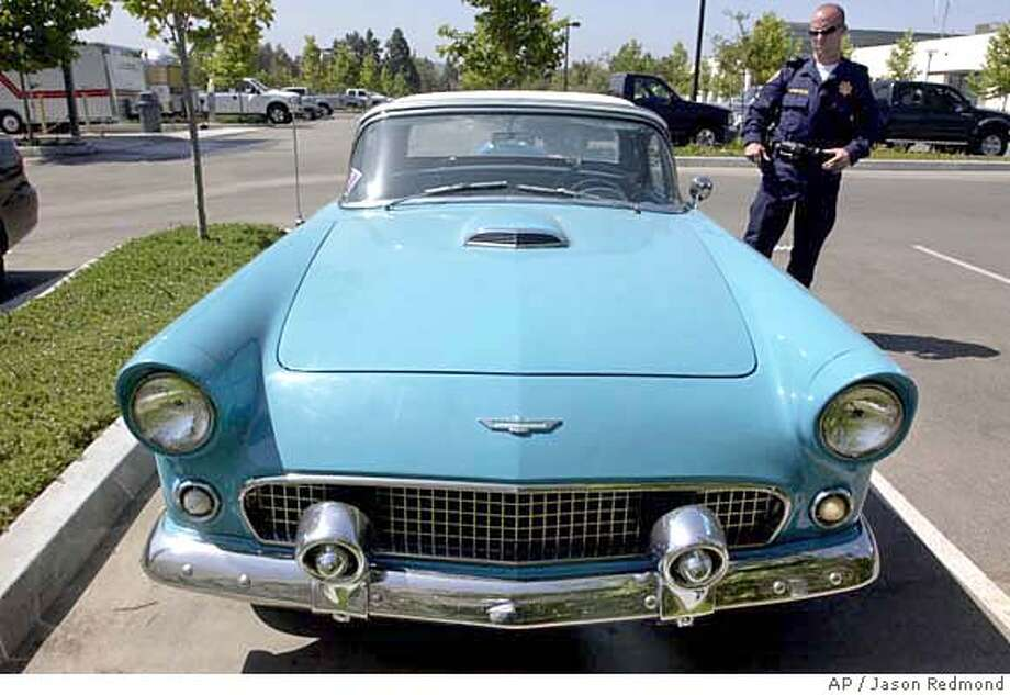California Highway Patrol Officer Christopher Throgmorton, right, stands next to a 1956 Ford Thunderbird on Tuesday, June 19, 2007, in Moorpark, Calif., that was reported stolen in Palo Alto, Calif., 31 years ago. The car, currently in the back parking lot of the Moorpark CHP station, was brought in by an area resident who recently purchased the vehicle through eBay and needed to locate the vehicle's identification number. Much to the new owner's surprise the vehicle turned up as stolen. If the original owner can be found, the vehicle will be either returned to them or to the insurance company that may have paid the claim. If no owner is found, the new buyers can keep the vehicle, police said. (AP Photo/Ventura County Star, Jason Redmond) ** MAGS OUT NO SALES LOS ANGELES TIMES OUT LOS ANGELES DAILY NEWS OUT MANDATORY CREDIT ** Photo: Jason Redmond