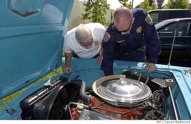 California Highway Patrol Officer Christopher Throgmorton, right, and volunteer Dave Dowding check under the hood of a 1956 Ford Thunderbird on Tuesday, June 19, 2007, in Moorpark, Calif., that was reported stolen in Palo Alto, Calif., 31 years ago. The car, currently in the back parking lot of the Moorpark CHP station, was brought in by an area resident who recently purchased the vehicle and needed to locate the vehicle's identification number. (AP Photo/Ventura County Star, Jason Redmond) ** MAGS OUT NO SALES LOS ANGELES TIMES OUT LOS ANGELES DAILY NEWS OUT MANDATORY CREDIT ** Photo: Jason Redmond