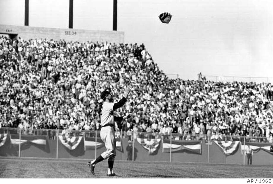 Pitcher Ralph Terry, of the New York Yankees, throws his glove high in the air after a shutout victory, 1-0, over the San Francisco Giants in the deciding game seven of the World Series at Candlestick Park, San Francisco, Ca., Oct. 16, 1962. (AP Photo)  Ran on: 06-22-2007  Splendor in The City: The Yankees and Giants line the basepaths for the National Anthem before Game 1 on Oct. 4, 1962. The Series began the day after the Giants won a three-game playoff against the Dodgers to capture the NL pennant. Photo: ASSOCIATED PRESS