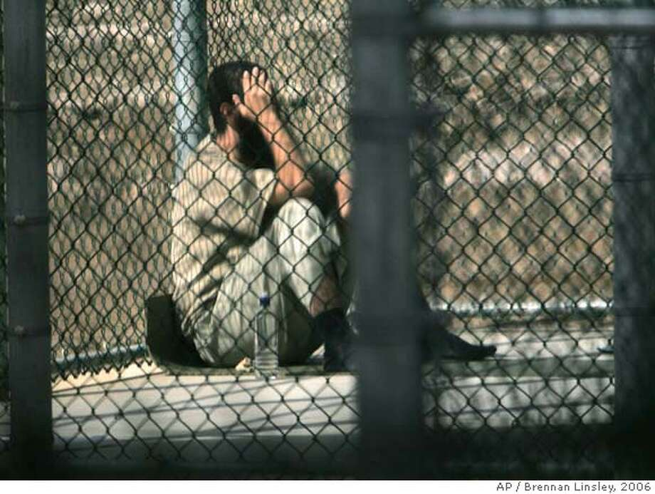 ** FILE ** In this Dec. 5, 2006 file photo, reviewed by a U.S. Dept of Defense official, a detainee sits alone inside a fenced area during his daily outside period, at Camp 5 maximum security detention prison, Guantanamo Bay U.S. Naval Base, Cuba. The Bush administration is nearing a decision to close the Guantanamo Bay detention facility and move the terror suspects there to military prisons elsewhere (AP Photo/Brennan Linsley, File) EFE OUT PHOTO REVIEWED BY US DEPT. OF DEFENSE OFFICIAL. Photo: Brennan Linsley