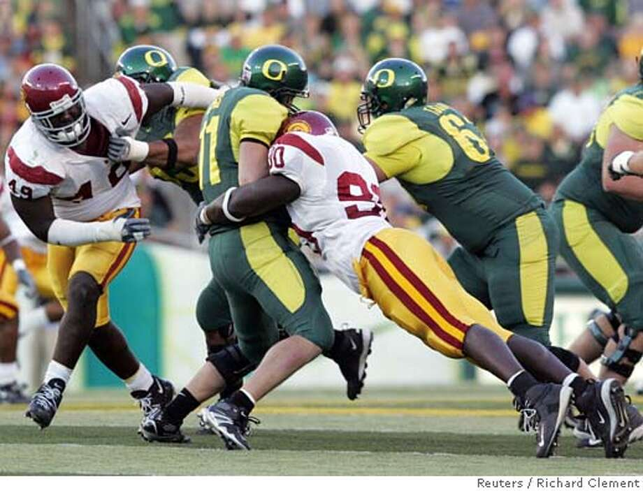 University of Oregon quarterback Kellen Clemens is sacked by University of Southern California's (USC) Frostee Rucker during the third quarter in Eugene, Oregon, September 24, 2005. USC's Sedrick Ellis (49) comes in to help, as Oregon's Josh Tschirgi (61) tries to defend. Top-ranked USC won 45-13. REUTERS/Richard Clement Ran on: 09-25-2005  USC teammates Dwayne Jarrett (8), Dominique Byrd (86) and Chris McFoy (82) gather to celebrate with Reggie Bush after Bush scored a third-quarter touchdown. Bush rushed for 122 yards. Ran on: 09-25-2005  USC teammates Dwayne Jarrett (8), Dominique Byrd (86) and Chris McFoy (82) gather to celebrate with Reggie Bush after Bush scored a third-quarter touchdown. Bush rushed for 122 yards. 0 Photo: RICHARD CLEMENT
