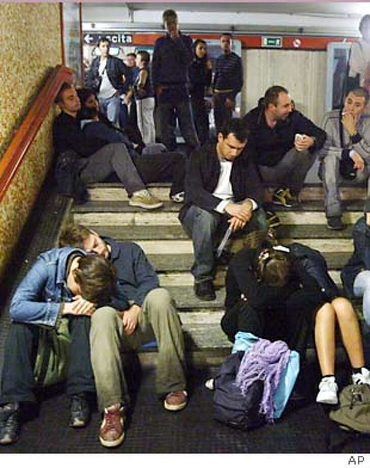 Stranded people who were making their way home from an all-night festival, wait for the rain to stop in Rome's Repubblica subway station, during a nationwide blackout, early Sunday Sept. 28, 2003. The causes of the blackout are still unknown. (AP Photo)