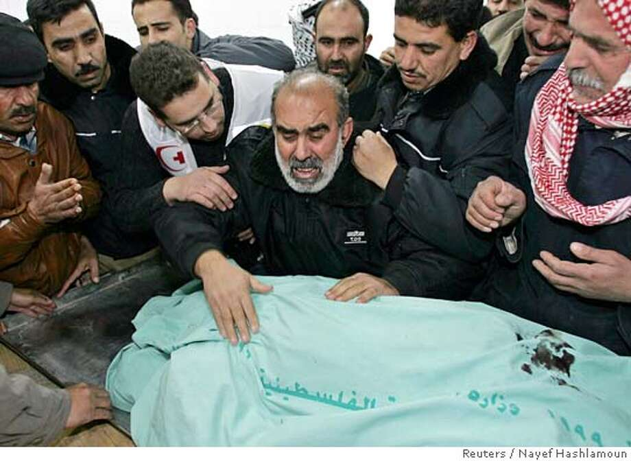 Relatives of Taha Asafrat, a Palestinian man killed in a suicide bomb attack near Tulkarm, cry over her body in a hospital in the West Bank city of Hebron December 29, 2005. A Palestinian suicide bomber blew himself up when Israeli troops tried to search him at a roadblock in the occupied West Bank on Thursday, killing an Israeli soldier and two other Palestinians. REUTERS/Nayef Hashlamoun Ran on: 12-30-2005  Relatives grieve over the body of a Palestinian man killed in the bomb attack in the West Bank. Photo: NAYEF HASHLAMOUN