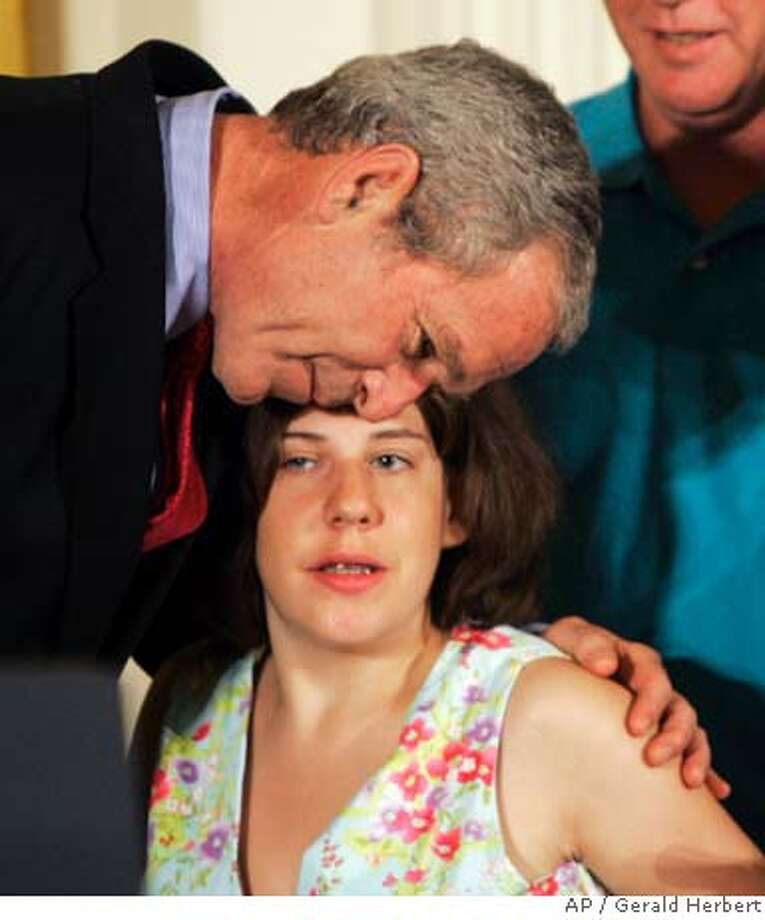 President Bush, left, hugs Kaitlyne McNamara of Middletown, Conn., who was born with spina bifida. after speaking on embryonic stem cell research, Wednesday, June 20, 2007, in the East Room at the White House in Washington. (AP Photo/Gerald Herbert) Photo: Gerald Herbert