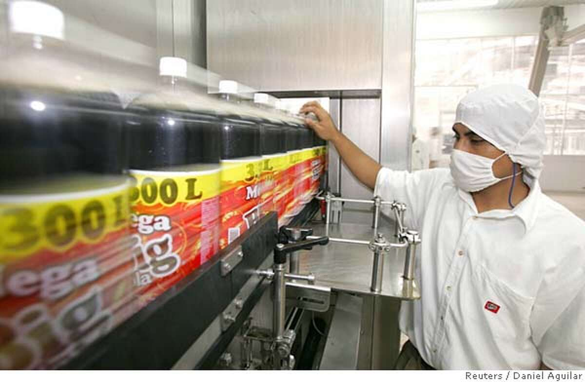 A Mexican worker checks the quality of Big-Cola bottles at a plant in Huejotzingo, Mexico, November 11, 2005. A little-known soft drinks bottler that has successfully taken on giants Coca-Cola and Pepsi in Mexico, the world's highest per capita consumer of Coke, now wants to challenge the country's top beermakers. Picture taken November 11, 2005 To match feature Mexico Coca-Cola REUTERS/Daniel Aguilar 0