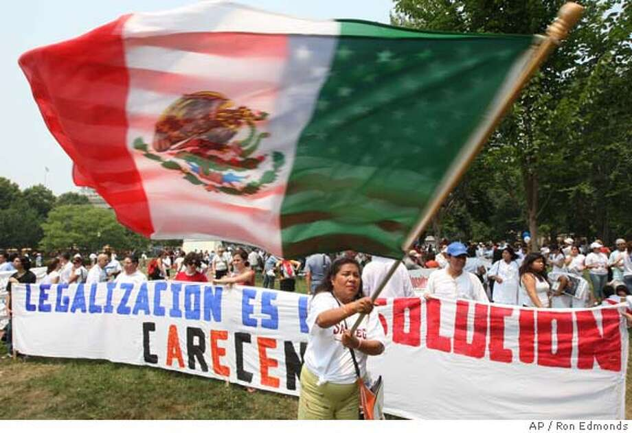 An immigration demonstrator waves flags during a rally in Lafayette Park across from the White House in Washington, Tuesday, June 19, 2007. (AP Photo/Ron Edmonds) Photo: Ron Edmonds