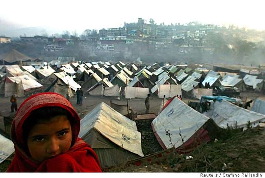 A girl stands in front of the Alkhedmat refugee camp in the earthquake-devastated city of Muzaffarabad, Pakistan-administered Kashmir, December 28, 2005. More than two months after Pakistan's killer earthquake, the focus of a huge aid effort is on keeping survivors alive in freezing mountains and preventing disease in crowded tent camps in the valleys. REUTERS/Stefano Rellandini 0 Photo: STEFANO RELLANDINI