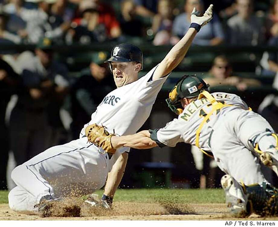 Seattle Mariners' John Olerud is safe at home plate as Oakland A's catcher Adam Melhuse can't make the tag in the first inning Saturday, Sept. 27, 2003 at Safeco Field in Seattle. Olerud was advancing on a Mariners' Randy Winn double. (AP Photo/Ted S. Warren) Photo: TED S. WARREN