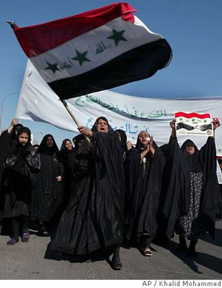 Iraqi Sunni women, one waving the national flag, take part in a rally in Baghdad, Iraq, Tuesday Dec. 27, 2005. More than 10,000 people backing Sunni Arab and secular Shiite politicians marched through Baghdad on Tuesday in support of a national unity government. Attacks on security forces continued, with five Iraqi police and two bystanders killed early Tuesday. Violence increased across Iraq after a lull following the Dec. 15 parliamentary elections. (AP Photo/Khalid Mohammed) Photo: KHALID MOHAMMED