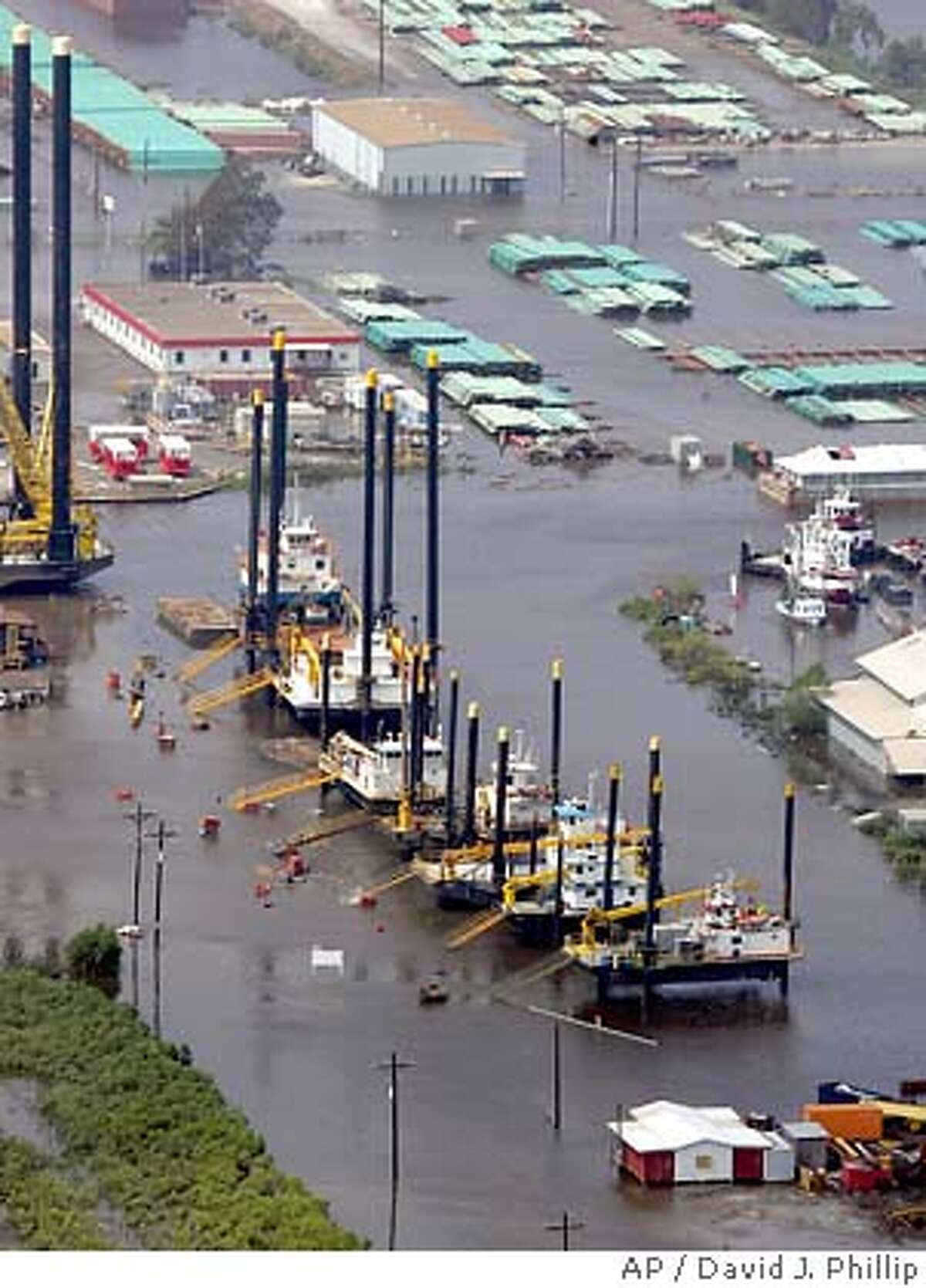 ** FILE **An oil rig platform contruction facility is surrounded by floodwaters in the aftermath of Hurricane Rita in a file photo from Sept. 25, 2005 near New Iberia, La. When drivers line up to pay $3 a gallon for gasoline and offshore oil rigs go missing, it's much more than an energy story. It's the story of the economy. (AP Photo/David J. Phillip, File) SEPT. 25, 2005 FILE PHOTO