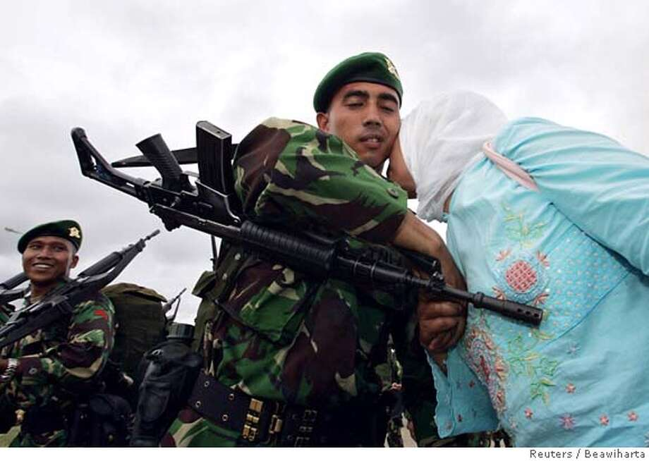 Indonesian soldier smiles as he watches Acehnese girl kiss his compatriot at Lhokseumawe port in Aceh Photo: BEAWIHARTA
