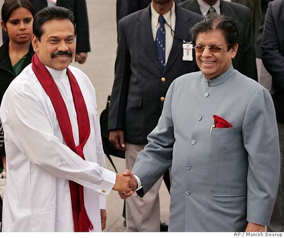 Sri Lankan President Mahinda Rajapakse, left, shakes hands with Indian Junior foreign minister E.Ahmed on his arrival in New Delhi, India, Tuesday, Dec. 27, 2005. Rajapakse is on a four-day official trip to India to strengthen economical and bilateral ties. (AP Photo/Manish Swarup) Photo: MANISH SWARUP