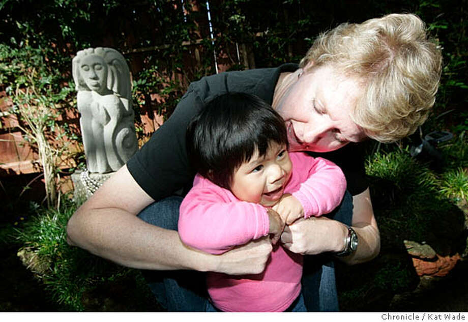 "FOGGARDEN_036_KW.jpg  On 10/19/05 in San Francisco Julie Jones with her newly adopted Guatemalan daughter Ava Jones, 19 months, in her ""fog garden"" that she used to release the stress of the adoption process. In the background is the beaded cement goddess made by Julie's cousin.  Kat Wade/The Chronicle Photo: Kat Wade"