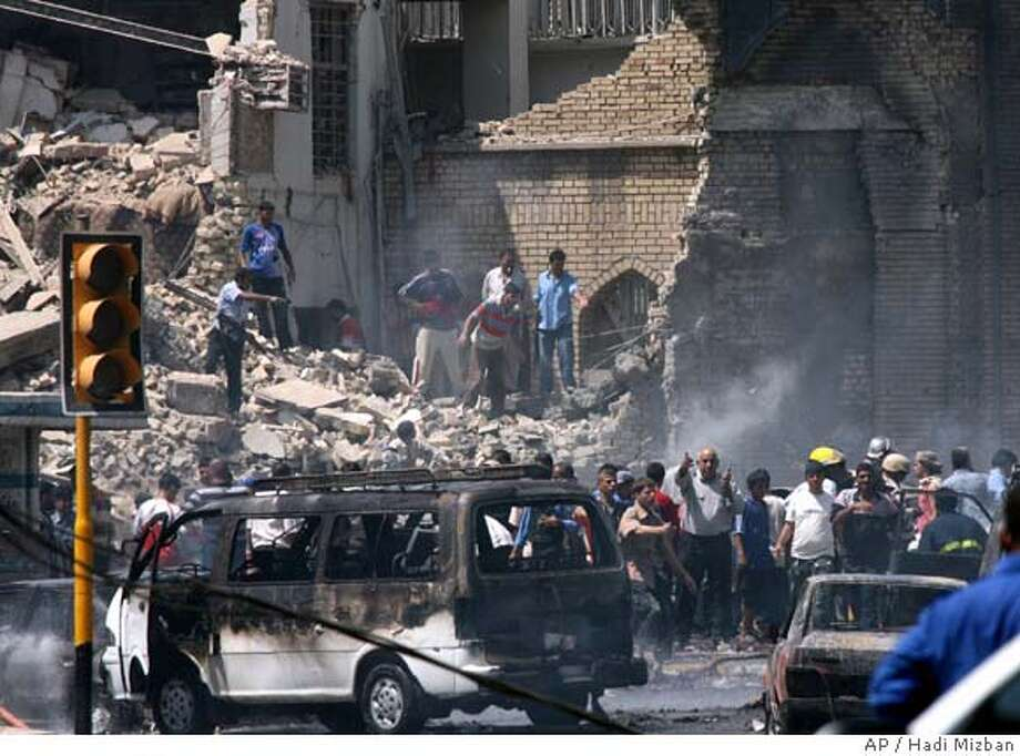 Iraqis gather at the damaged Khillani mosque, a main Shiite mosque in central Baghdad, Iraq, Tuesday, June 19, 2007. A truck bomb struck a Shiite mosque Tuesday in central Baghdad, killing 75 people and wounding more than 200, even as about 10,000 U.S. soldiers northeast of the capital used heavily armored Stryker and Bradley fighting vehicles to battle their way into an al-Qaida sanctuary. (AP Photo/Hadi Mizban) Photo: HADI MIZBAN