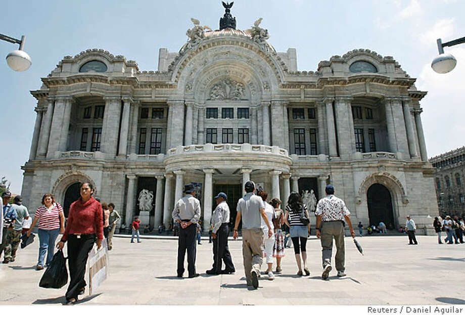 People walk past Mexico City's Bellas Artes museum June 12, 2007. The Mexican capital will host the largest ever exhibition of Frida Kahlo's works, held at Bellas Artes museum, this week to mark 100 years since the birth of the artist. The exhibition will run from June to August. REUTERS/Daniel Aguilar (MEXICO) Photo: DANIEL AGUILAR