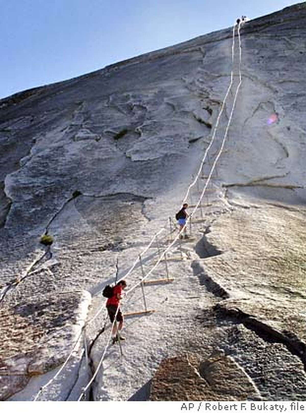 ** FOR IMMEDIATE RELEASE **Hikers decend the cable route after climbing to summit of Half Dome, June 6, 2004, in Yosemite National Park. In 1875 George Anderson first climbed this route by drilling holes in the granite and attaching ropes to pull himself to the summit. The park has maintained permanent cables here since 1919. (AP Photo/Robert F. Bukaty)