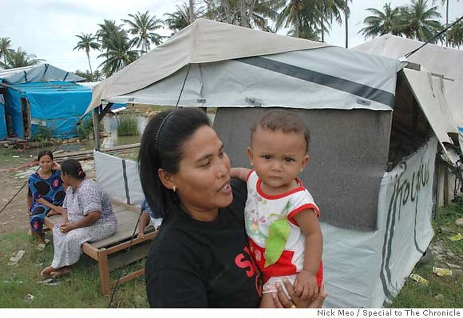 Picture shows Mrs Nilawati Sulaiman in front of her tent home, with Willi - an infant whose parents are dead and who she has adopted. Thousands of Acehnese made refugees in last year's tsunami are still living in bad conditions. Photo by Nick Meo/Special to The Chronicle Photo: Nick Meo/Special To The Chronicl