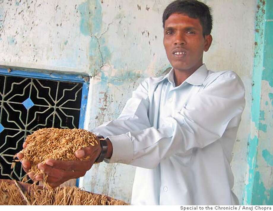 Kiran Mhatre, 33, a local farmer showing me his surplus rice produce. He grows nearly 12 quintals on rice on his 3 acre farm every year -- more than enough to feed his family of five for the whole year. Photo credit: Anuj Chopra, Special to the Chronicle  Ran on: 06-18-2007  Kiran Mhatre earns $600 a year and feeds a family of five on 3 acres. A company recently offered him $24,000 for it. He said no. Photo: Anuj Chopra