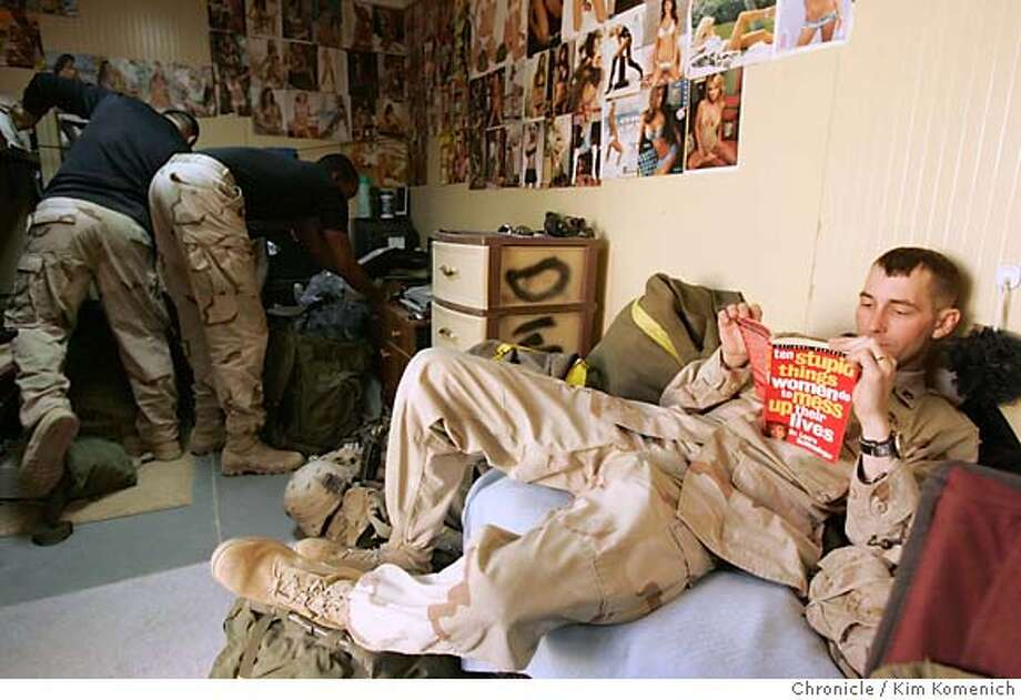 "IRAQXX_WAR_0092_KK.JPG  While his roommates Sgt. Darrell Foster (L) and Sgt. Quaithan Sargent (R), (both w/backs to camera) continue to pack, Sgt. Kenneth Gainey, 27, from Quincy, Fla., reads Dr. Laura Schlessinger's ""10 Stupid things Women Do to Mess up their Lives. Soldiers from the Army's 2-7 Infantry Battalion of the First Brigade,Third Infantry Division pack up their non-essential gear to be sent by ship to the U.S. Soldiers from the 2-7 will begin departing F.O.B. Remagen in Tikrit in two weeks.  San Francisco Chronicle photo by Kim Komenich  12/6/05 Photo: Kim Komenich"