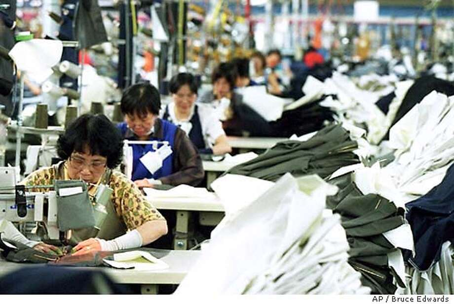 FILE--Workers sew clothes at the Levi Strauss & Co. plant in Edmonton in this Apr.16, 1999 file photo. The plant will close in March 2004, putting 488 people out of work. (CP PHOTO/Edmonton Journal/Bruce Edwards) Photo: BRUCE EDWARDS