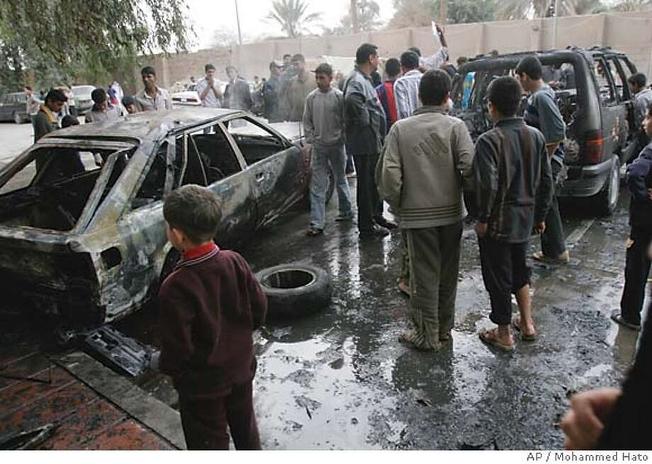 Iraqis inspect the wreckage of two cars at the site of a mortar shell attack in Baghdad, Iraq, Sunday Dec. 25, 2005. A mortar round hit a housing complex in the Salihyaa district wounding two civilians and damaging two cars.(AP Photo/Mohammed Hato) Photo: MOHAMMED HATO