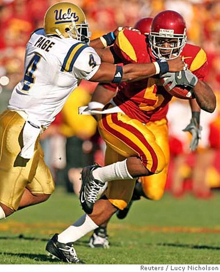 University of Southern California tailback Reggie Bush (5) breaks a tackle from UCLA's Jarrad Page during the first quarter of their NCAA game in Los Angeles, December 3, 2005. REUTERS/Lucy Nicholson Ran on: 12-04-2005  Reggie Bush did it all in Saturday's Southern California showdown, including leaping over Bruins defenders for one of his two touchdowns. Ran on: 12-04-2005  Reggie Bush did it all in Saturday's Southern California showdown, including leaping over Bruins defenders for one of his two touchdowns. Ran on: 12-04-2005  Reggie Bush did it all in Saturday's Southern California showdown, including leaping over Bruins defenders for one of his two touchdowns. 0 Photo: LUCY NICHOLSON