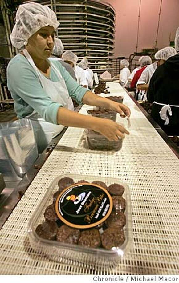 dessert08_080_mac.jpg Luz Maria Arriaga works the assembly line packaging the boxes of Brownie Bites. After filing for bankruptcy in 2003, Just Desserts of Oakland makes a a big comeback, with last year's revenues up by 40 percent. The company is hoping to get more of it's products into national grocery chains. Photographed in, Oakland, Ca, on 6/7/07. Photo by: Michael Macor/ The Chronicle Ran on: 06-17-2007  A worker packages up Brownie Bites at the Just Desserts bakery in Oakland. The company, which started in San Francisco in 1974 and fell on hard times in recent years, is making a big comeback, much to the relief of fans of their desserts with an &quo;out-of- this-world aura.&quo; Photo: Michael Macor