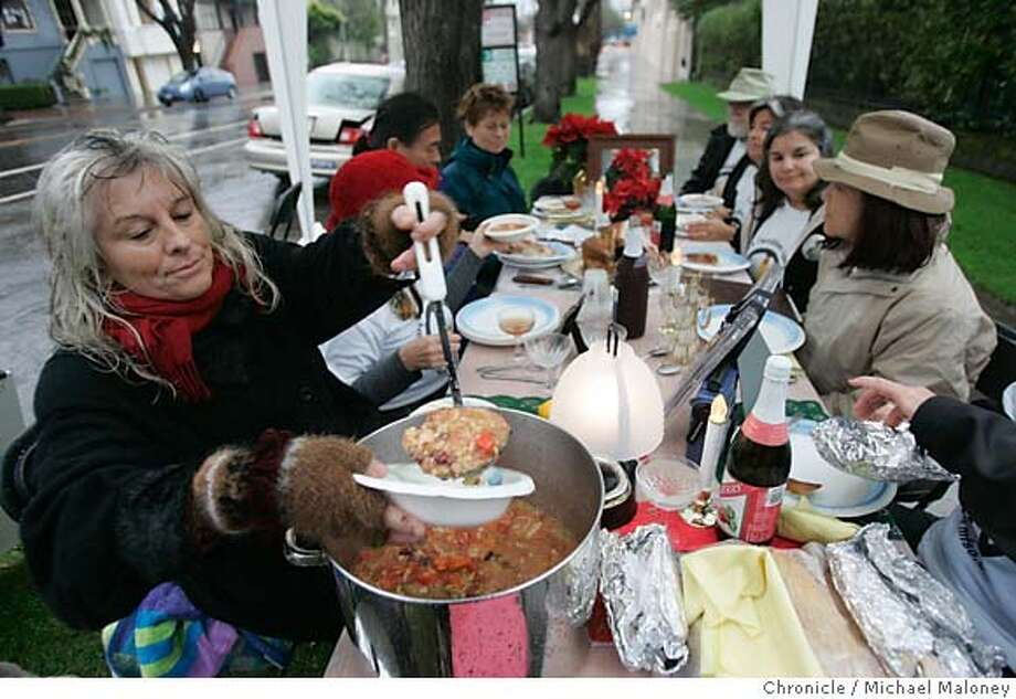 Mia Lorraine of Sebastopol (left) dishes bowls of soup for her friends.  Nine supporters of the anti-war group Military Families Speak Out, had a wet Christmas dinner under a tent in front of US Senator Dianne Feinstein's SF house. They served a full course traditional holiday meal including turkey, tamales, soup and apple cider. They were urging Senator Feinstein to bring all the troops home now. Military Families Speak Out is an organization of people who have relatives or loved ones in the military and who are opposed to war in Iraq.  Event in San Francisco, CA  Photo by Michael Maloney / The Chronicle Photo: Michael Maloney