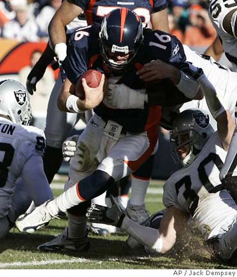 Denver Broncos quarterback Jake Plummer (16) scores on a 1-yard run as Oakland Raiders safety Stuart Schweigert (30) tries to keep him out of the end zone in the first quarter of Saturday's NFL football game in Denver, Dec. 24, 2005. (AP Photo/Jack Dempsey) Photo: JACK DEMPSEY