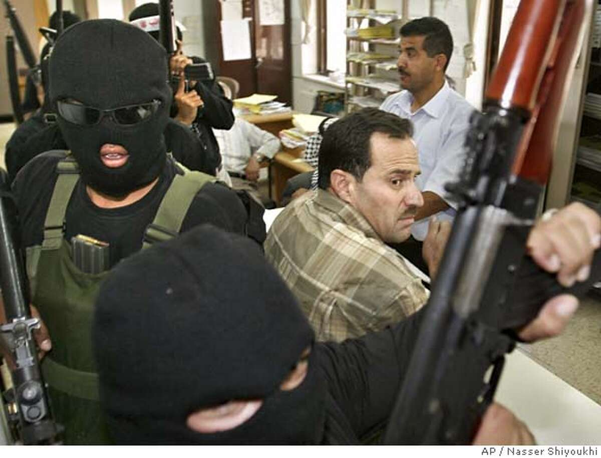 Palestinian militants from the Al Aqsa Martyrs Brigades, a group linked to the Fatah Movement, stand with their weapons inside an office of the Ministry of the Finance as they search for employees with Hamas affiliation in the West Bank city of Hebron, Saturday, June 16, 2007. Hundreds of Fatah gunmen on Saturday stormed Hamas-controlled institutions in the West Bank, including parliament and government ministries, and told staffers that those with ties to Hamas will not be allowed to return. The gunmen planted Fatah flags and Palestinian banners on the buildings they had taken over. (AP Photo/Nasser Shiyoukhi)