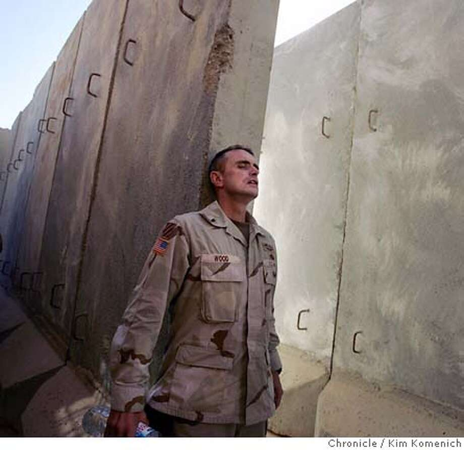 """Lt. Col. Todd Wood, commander of the 2-7 Infantry Battalion of the First Brigade, Third Infantry Division, U.S. Army stretches against a """"T-wall"""" outside the battalion command center. He wasn't particularly stressin'. San Francisco Chronicle Photo by Kim Komenich  12/2/05 Photo: Kim Komenich"""