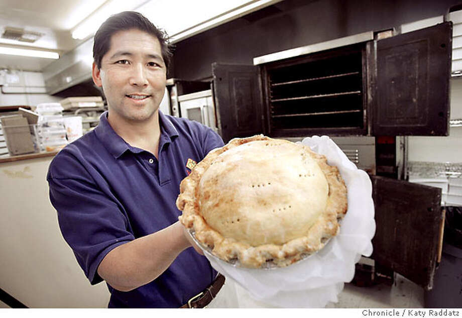 AUBURN_077_RAD.jpg SHOWN: Glen Ikeda, the owner of Ikeda's California Country Market, proudly shows off a homemade apple pie, with the baking ovens in the background. Ikeda's is a produce stand and bakery and market .Travel story about the tiny town of Auburn, CA. These pictures were made in Auburn, CA. on Wednesday, May 30, 2007. (Katy Raddatz/The Chronicle)  **Glen Ikeda Photo: Katy Raddatz