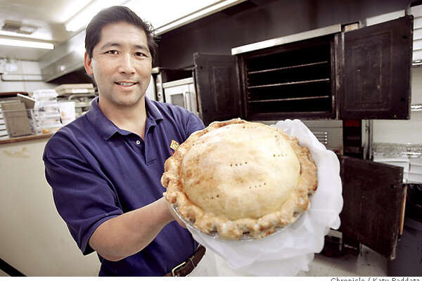 AUBURN_077_RAD.jpg SHOWN: Glen Ikeda, the owner of Ikeda's California Country Market, proudly shows off a homemade apple pie, with the baking ovens in the background. Ikeda's is a produce stand and bakery and market .Travel story about the tiny town of Auburn, CA. These pictures were made in Auburn, CA. on Wednesday, May 30, 2007. (Katy Raddatz/The Chronicle)  **Glen Ikeda