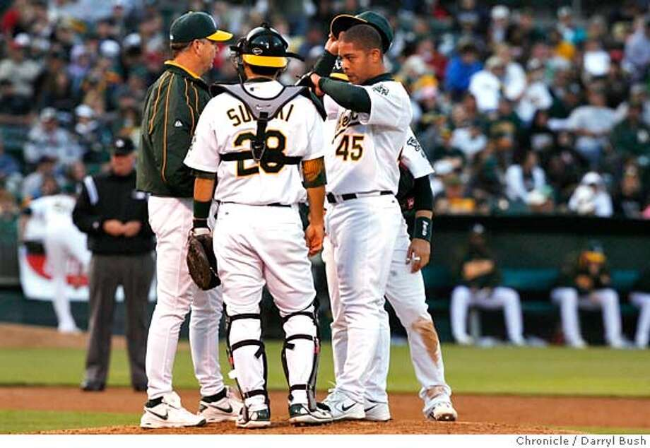 athletics_0006_db.JPG  Oakland Athletics' Ruddy Lugo (45) reacts to a rough inning as he meets on the mound with Athletics' catcher, Kurt Suzuki (28) and others in the 5th inning, Oakland Athletics vs. St. Louis Cardinals at McAfee Coliseum in Oakland, CA, on Saturday, June, 16, 2007. photo taken: 6/16/07  Darryl Bush / The Chronicle ** (cq) Photo: Darryl Bush