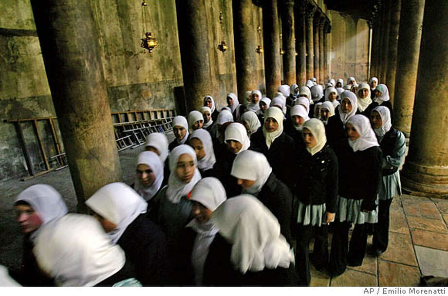 Muslim Palestinian school girls visit the Church of the Nativity, believed to be the birthplace of Jesus Christ, in the West Bank town of Bethlehem Tuesday Dec. 13, 2005. The last five years of violence and the separation barrier Israel is building have affected the number of tourists visiting Bethlehem, traditionally a popular destination for Christians during the Christmas season.(AP photo/Emilio Morenatti) Photo: EMILIO MORENATTI