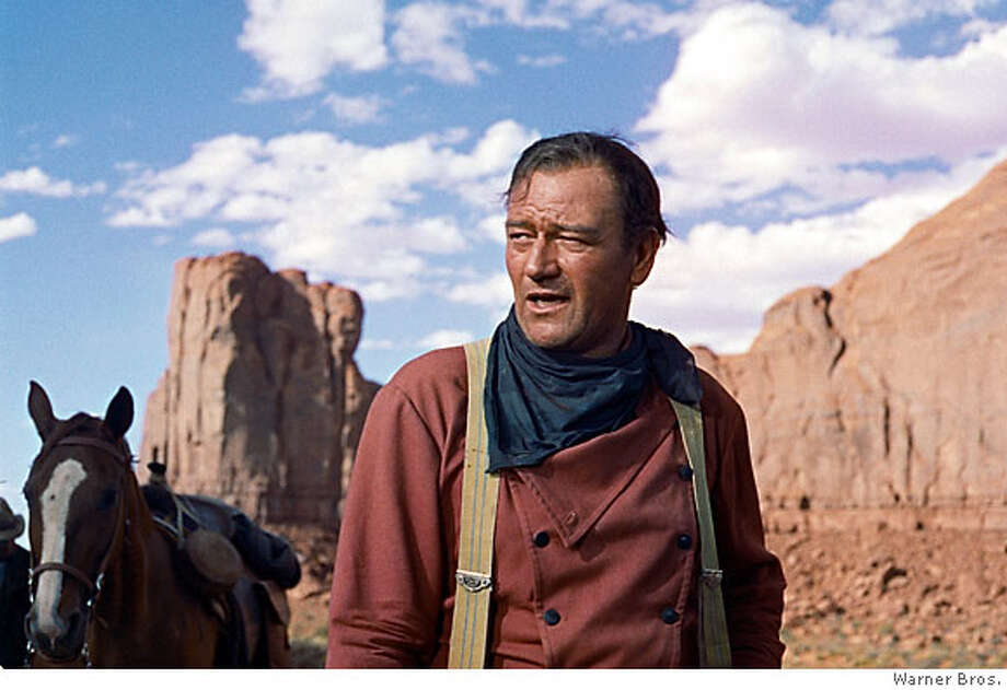 "**FILE**In this photo released by Warner Bros., actor John Wayne plays Ethan Edwards in the 1956 film ""The Searchers."" Director John Ford and frequent leading man Wayne forged one of Hollywood's most enduring partnerships. Wayne, born Marion Robert Morrison, would have turned 100 on Saturday, May 26, 2007. He died at the age of 72 of stomach cancer in June of 1979 after a career that spanned more than 170 films (AP Photo/Warner Bros.) Photo: Warner Bros."