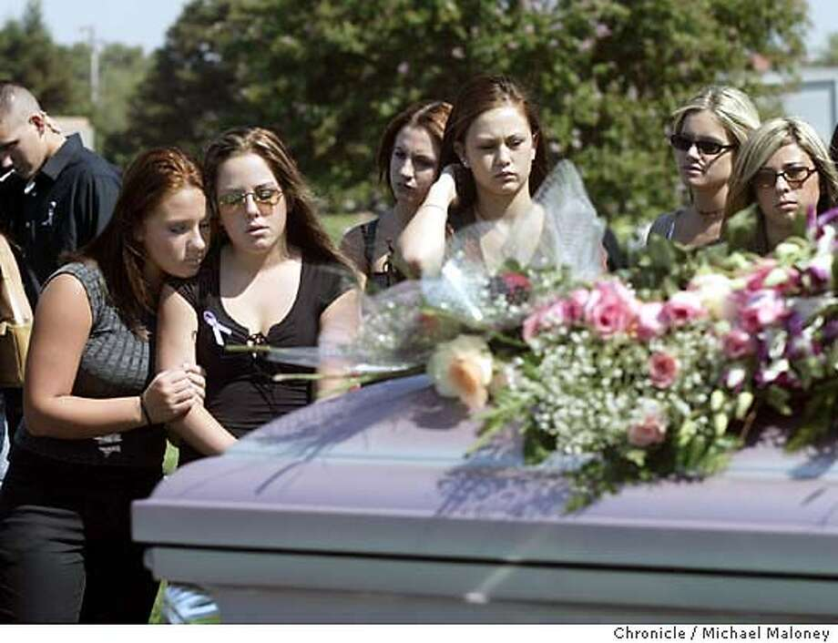 Solemn faces belonging to friends of Holly Patterson look over the flower draped casket after the funeral service.  Funeral of Holly Patterson, an 18 year old woman who died days after taking the abortion pill, RU-486. Services and funeral took place at Callaghan Mortuary and Memory Gardens Cemetery in Livermore.  Event on 9/24/03 in Livermore.  MICHAEL MALONEY / The Chronicle Photo: MICHAEL MALONEY