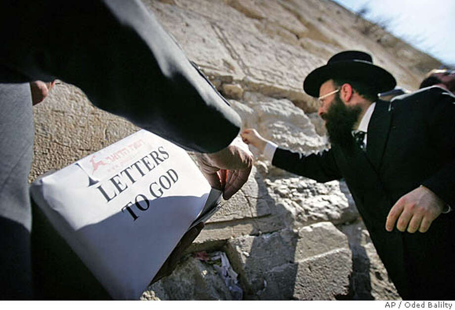 Shmuel Rabinovich, the rabbi of the Western Wall, Judaism's holiest site, places letters, written by worshippers from around the world and addressed to God, into holes in the Wall, in Jerusalem's Old City, Wednesday, Dec 14, 2005. Israeli postal workers say that hundreds of letters written to God, most addressed simply to Jerusalem, arrive in Israel each year, frequently around Jewish and Christian holidays. The letters are collected, read, and periodically taken to the Western Wall in Jerusalem. (AP Photo/Oded Balilty) Photo: ODED BALILTY