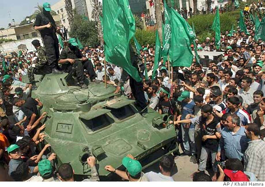 Hamas militants stand on an armored vehicle seized in fighting with security forces loyal to Palestinian President Mahmoud Abbas in recent days, at a rally in Gaza City, Friday, June 15, 2007. The Palestinian territories have essentially been split into two parts. Gaza is now under the control of Hamas, an Islamic movement with close ties to Syria and Iran. The West Bank, home to most of the Palestinian population, is dominated by the more moderate Fatah, which has ties to Israel and the West. (AP Photo/Khalil Hamra) Photo: KHALIL HAMRA