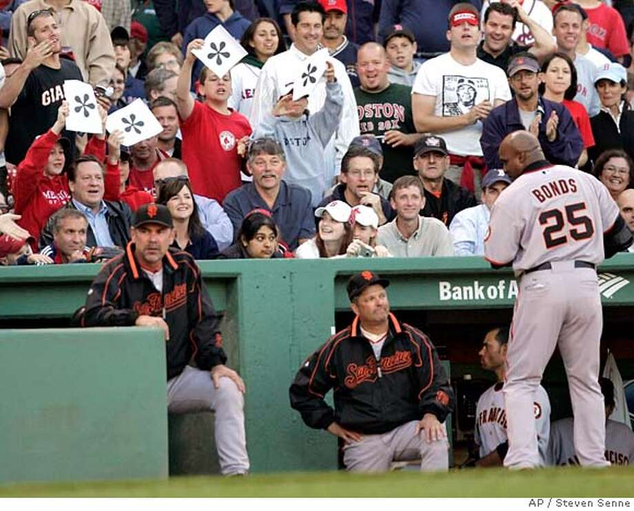 Baseball fans in the stands hold up signs featuring asterisks as San Francisco Giants Barry Bonds returns to the dugout in the first inning of a baseball game against the Boston Red Sox at Boston's Fenway Park, Friday, June 15, 2007. Bonds flied out to right field in the first inning. (AP Photo/Steven Senne) Photo: Steven Senne