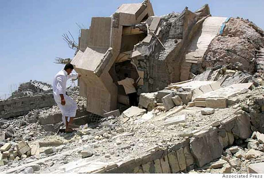 Men survey the damage to the destroyed Talha Bin al-Zubair shrine about 20 kilometers (13 miles) outside Basra, Iraq, 550 kilometers (340 miles) southeast of Baghdad, Friday, June 15, 2007. Gunmen armed with rocket-propelled grenades attacked the shrine late Thursday, partially damaging the building and returned early Friday, planting bombs inside the structure to completely destroy the building, police said. (AP Photo) Photo: STR