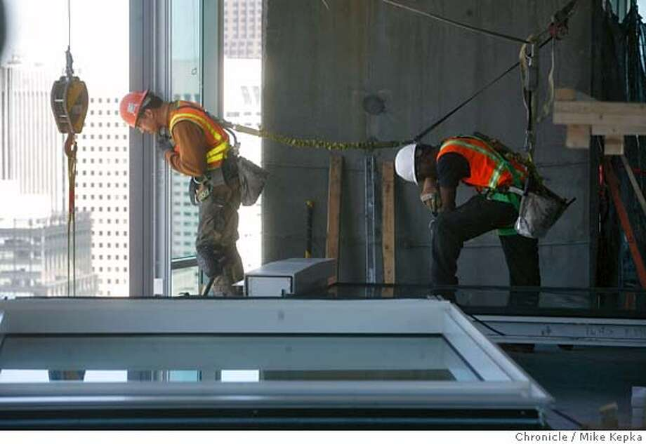 rincon000269.JPG Iron workers David Plousha and Paul Hicks Jr. the allignment of a glass panal on the 48th floor of RIncon One where workers have been installing a glass facing, called the curtain wall. Each interlocking piece of glass weighs hundreds of pounds. The project is about 2/3 complete. Mike Kepka / The Chronicle David Plousha Paul Hicks Jr. (cq) MANDATORY CREDIT FOR PHOTOG AND SF CHRONICLE/NO SALES-MAGS OUT Photo: Mike Kepka