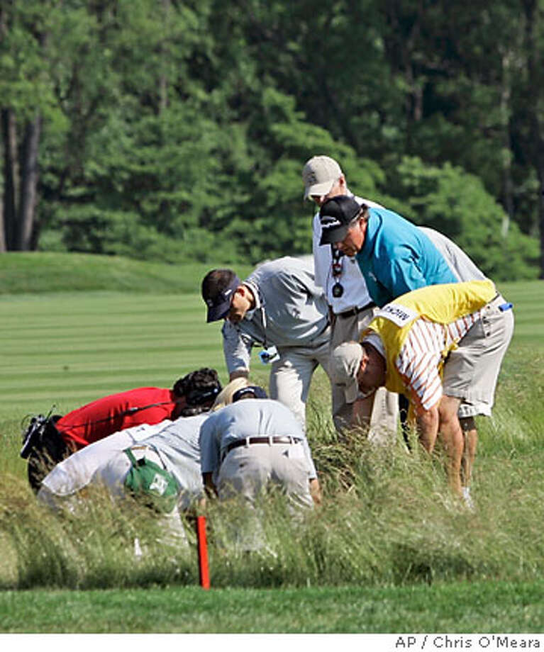 Officials look for Phil Mickelson's ball in a hazard on the eighth fairway during the second round of the 107th U.S. Open Golf Championship at the Oakmont Country Club in Oakmont, Pa., Friday, June 15, 2007. Mickelson, right, took a drop. (AP Photo/Chris O'Meara) Photo: Chris O'Meara