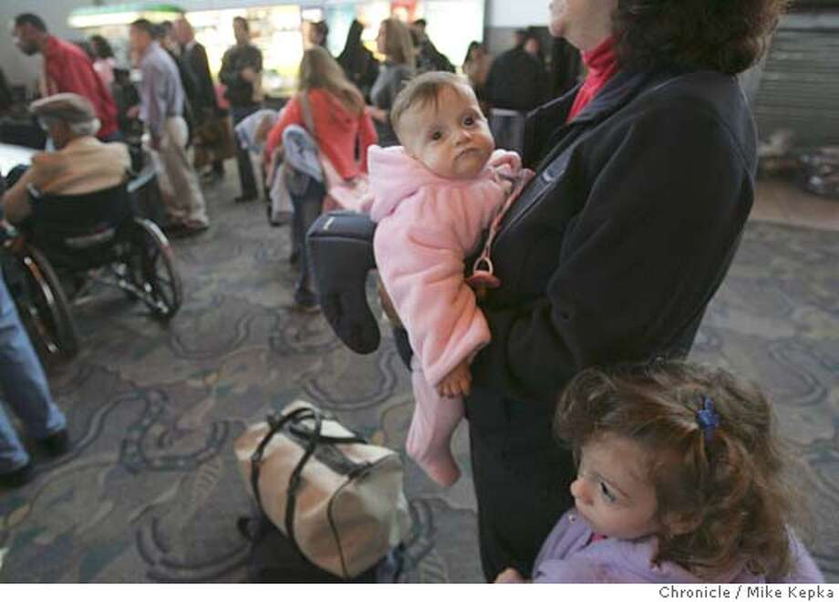 airport23017seqn}_mk.JPG Holding her kids Evangeline Asprogerakas, 9 months and Elianna Asprogerakas. 3. Sophie Asprogerakas waits for her parents' luggage to arrive form Kansas City.  Oakland International Airport seems to be busier than ever with holiday travel despite a new security ease on scissors and tools. Oakland on 12/22/05. Mike Kepka / The Chronicle MANDATORY CREDIT FOR PHOTOG AND SF CHRONICLE/ -MAGS OUT Photo: Mike Kepka