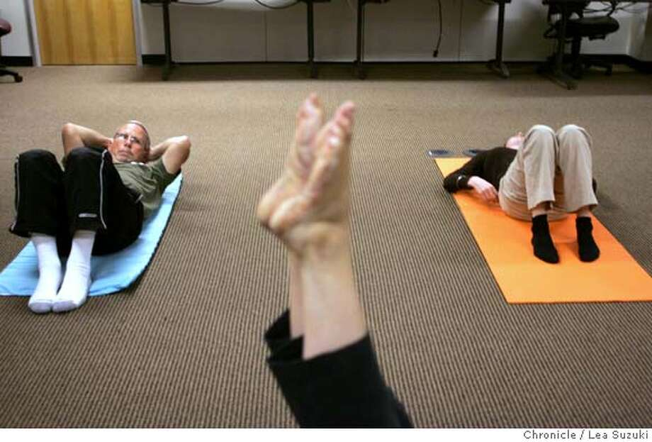 Foreground: feet of Kerri Williams, instructor at Studio 4 Pilates in Half Moon Bay (left) Dan Crouch, PR Manager; (right) Mhari Scott, Marketing Coordinator. Crouch and Scott watch and listen as Williams performs a move as she teaches a Pilates class in the media room at Camico Mutual Insurance Co. Camico Mutual Insurance Company's workplace wellness program includes on-site Pilates classes, an on-site gym, and also has a walking trail next to the office.  Photo taken on 061307 in Redwood City, CA.  Photo by Lea Suzuki/ The Chronicle  (Kerri Williams, Dan Crouch, Mhari Scott)cq Photo: Lea Suzuki