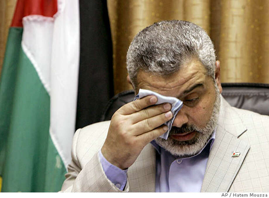 "Deposed Palestinian Prime Minister Ismail Haniyeh from the Hamas wipes his brow during a press conference in Gaza City, early Friday, June 15, 2007. At a news conference in Gaza City early Friday, Haniyeh rejected President Mahmoud Abbas' declaration, calling it ""hasty"" and saying he would maintain a unity government. Haniyeh said the situation was ""not suitable for unilateral decisions."" He said the Hamas militia would impose law and order ""firmly, decisively and legally."" He also rejected the idea of a Palestinian state in Gaza only, run by Hamas.(AP Photo/Hatem Moussa) Photo: Hatem Moussa"