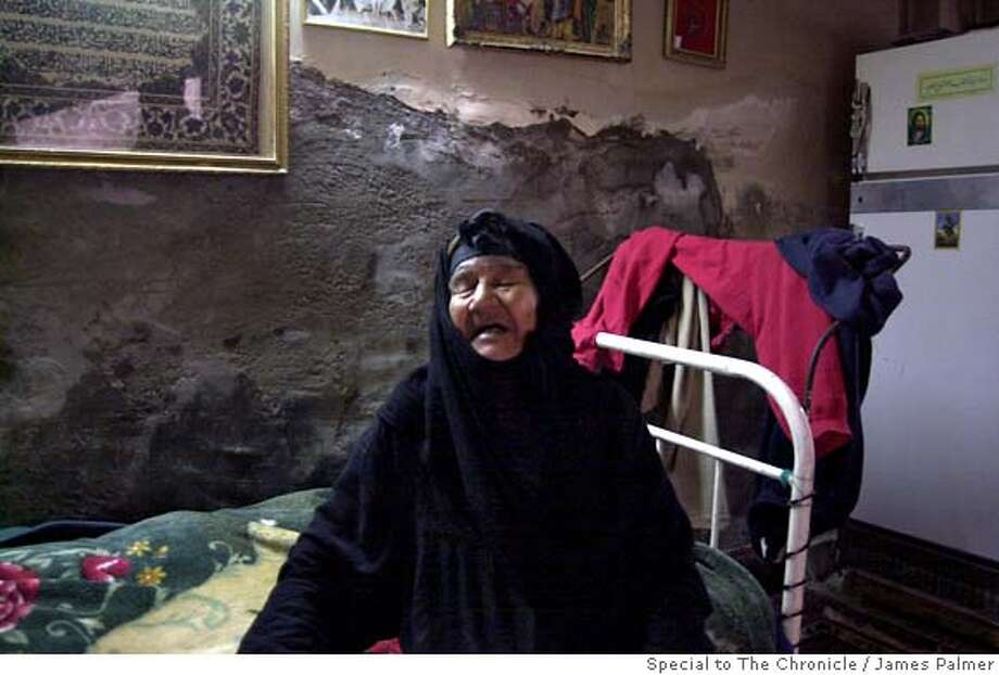 Mariam Ansari, 87, sitting inside her room in Baghdad, Iraq, on April 23, 2007. Ansari lives in a single room where a fluorescent light illuminates a twin bed and a patchwork of threadbare Persian rugs over a dirt floor surrounded by cement walls. The room, given by a neighbor as charity, is among one of many donations from the community that Ansari depends upon to meet her basic needs. But these contributions are not enough to save Ansari the indignation of begging at a local marketplace. �What can I do?� Ansari asked. �I accept my life for good or bad. This is God�s will.� Traditionally dependent upon family members to care for them, the elderly in Baghdad are frequently abandoned as their younger relatives flee the ongoing violence in the Iraqi capital, or simply move to safer ground within the city. In other instances, families here are pressed to cast aside their elder members as economic hardships grow.  JAMES PALMER / SPECIAL TO THE CHRONICLE NO MAGS, NO SALES, NO TV Photo: James Palmer