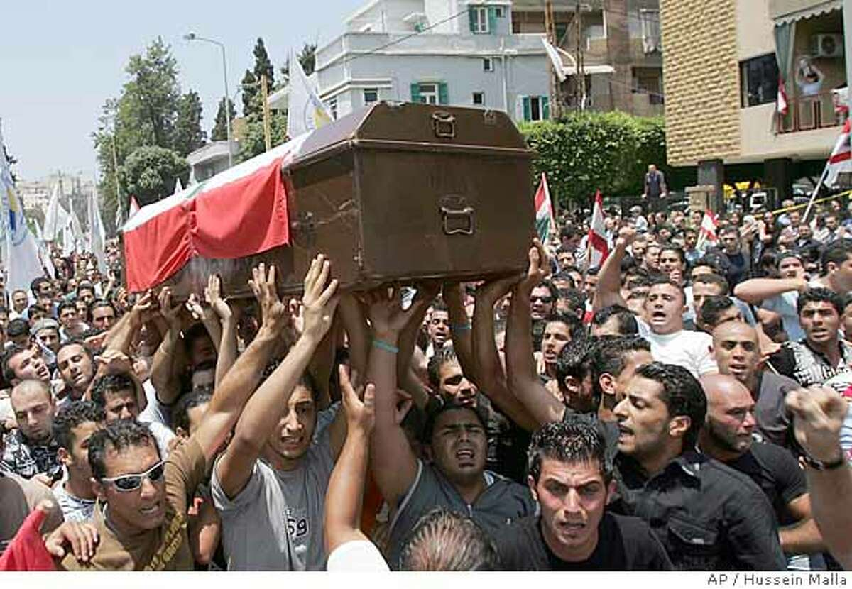 Lebanese people carry the coffin of slain anti-Syrian lawmaker Walid Eido who was killed by an explosion on Wednesday, as they head to a mosque during his funeral procession in Beirut, Lebanon Thursday, June 14, 2007. Tens of thousands bade farewell on Thursday to victims of a powerful car bombing that killed a prominent anti-Syrian legislator and nine other people as the government _ reeling from another blow targeting its supporters _ sought international help. (AP Photo/Hussein Malla)