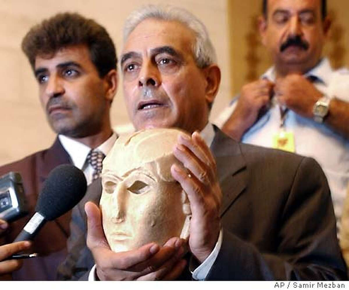 """Iraqi Minster of Culture Mufeed Muhammad Jawad Al Jazairee holds the """"Warka Mask"""", a 3100 B.C. Sumerian artifact which was looted from the Iraq national Museum in the final days of Saddam Hussein's regime, as it is returned by Iraqi police Tuesday Sept. 23, 2003. Iraqi police, supported by U.S. military police, recoved the limestone sculpture of a woman's head outside of Baghdad and is considered one of the most important looted pieces returned thus far. (AP Photo/Samir Mezban)"""